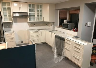 kitchen renovation in progress with white cabinets and glass paneled cabinet doors