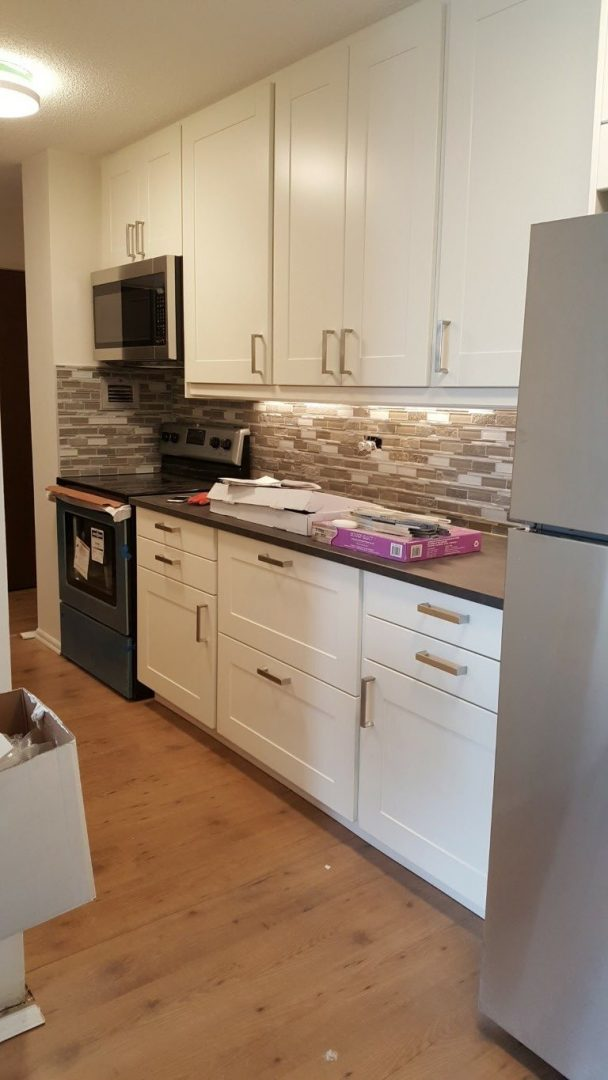 white kitchen cabinets and counters with simple tile back splash