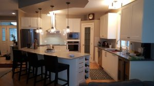 medium sized kitchen with white cabinets and curved island counter