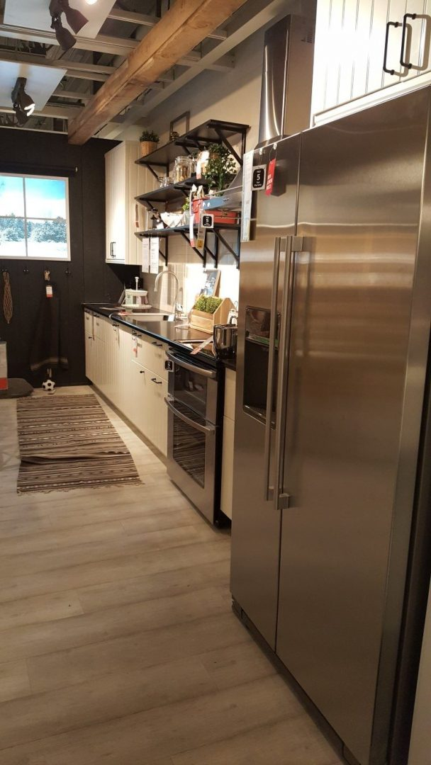 ikea kitchen display with wood paneled flooring and white counters