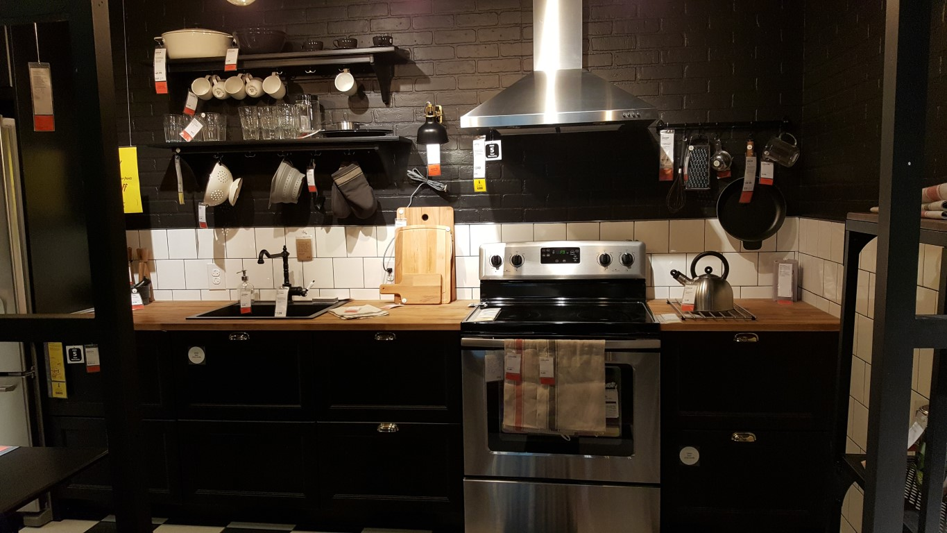 modern ikea kitchen display with dark cabinets and light wood counter tops