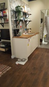 ikea white counter with wooden counter tops, black shelves placed above them