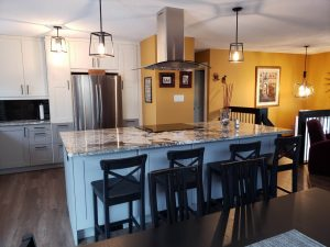 large sized kitchen with white kitchen island with marble counter tops