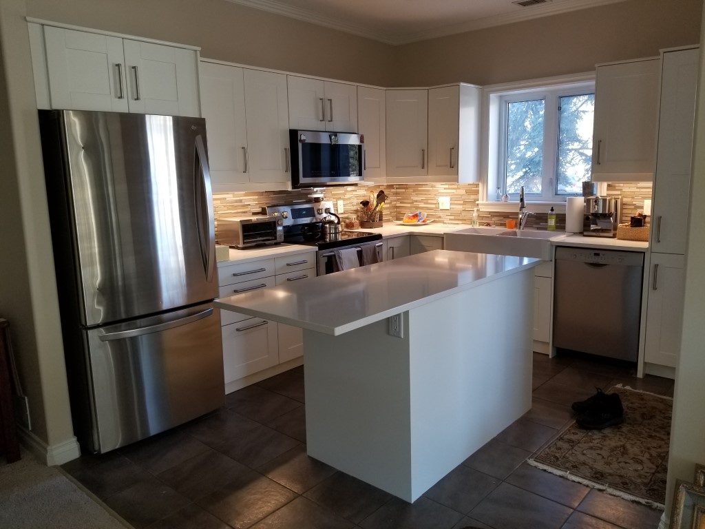 medium sized kitchen with white cabinets and small kitchen island in the center