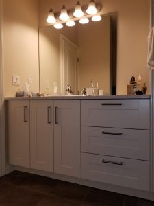 white bathroom cabinets with large mirror above