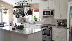 small kitchen with white cabinets and simple white tile back splash